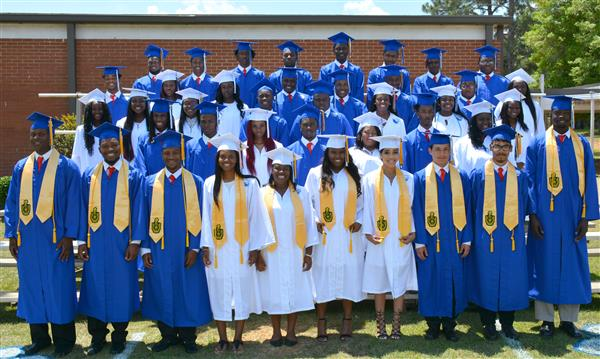 Class of 2017 standing on risers in cap and gowns.