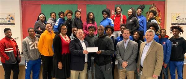 Students standing behind Georgia Power executives donating check to Athletic Director Marcus Shaw.