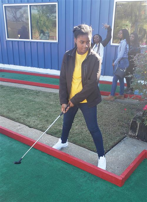 Girl in yellow shirt standing with putter,