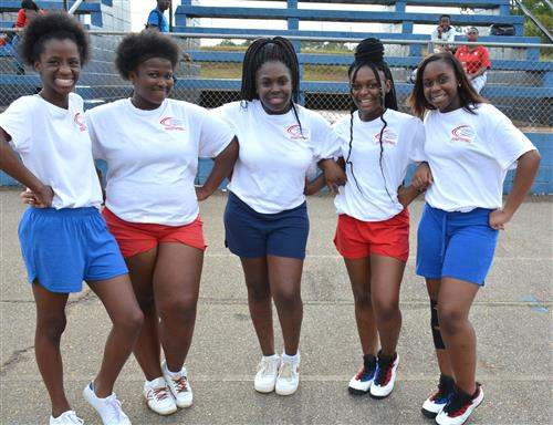 Five girls in a semi circle dressed in cheerleading shorts